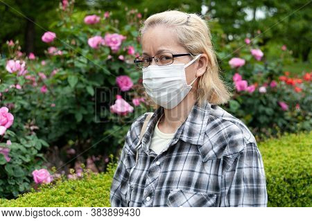 Middle Aged Mixed Race Blonde Woman With Eyeglasses Wearing White Surgical Mask. Protection Against