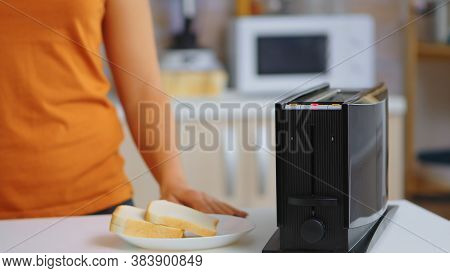 Woman Waiting For Roasted Bread To Pop From Electric Toaster. Housewife Using Bread Toaster For Deli