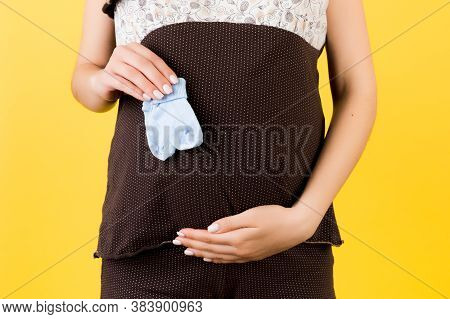 Cropped Image Of Blue Socks For A Baby Boy In Pregnant Womans Hand Against Her Belly At Yellow Backg