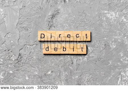 Direct Debit Word Written On Wood Block. Direct Debit Text On Cement Table For Your Desing, Concept