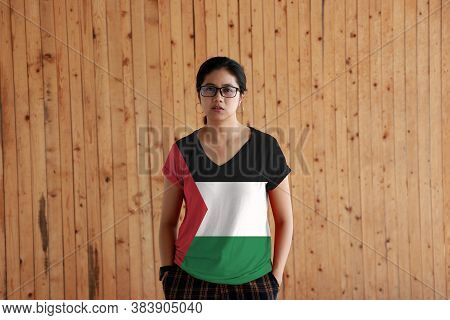 Woman Wearing Palestine Flag Color Shirt And Standing With Two Hands In Pant Pockets On The Wooden W