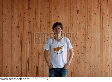 Man Wearing Cyprus Flag Color Shirt And Standing With Two Hands In Pant Pockets On The Wooden Wall B