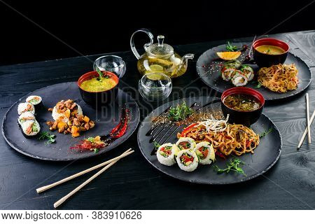 Traditional Japanese Food - Sushi, Rolls, Rice And Udon Noodles On A Dark Background. Top View Of As