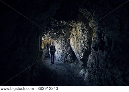 Young Man Is Looking Into Light At The End Of The Tunnel. Young Hiker Walking  Through Tunnel In Roc