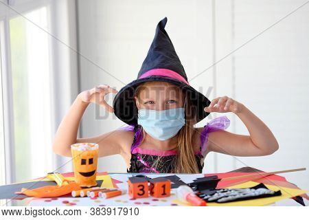 A Little Girl In A Witch Costume In A Medical Mask Makes Crafts And Scares.