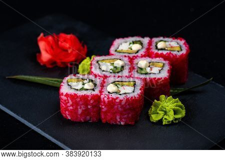 Japanese Sushi In Red Flying Fish Roe Isolated On Dark Background. California Roll With Salmon, Cucu