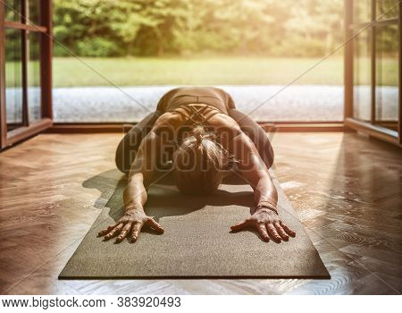 Young Woman Practicing Yoga At Home On A Sunny Day