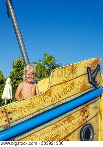 Pirate Day. A Little Boy Looking Like A Pirate With A Parrot Is Standing On A Sinking Ship In The Po