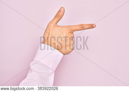 Hand of caucasian young man showing fingers over isolated pink background pointing with index finger to the side, suggesting and selecting a choice