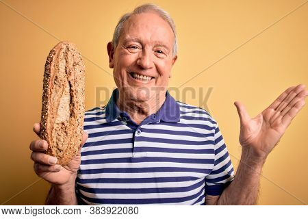 Grey haired senior man holding healthy wholemeal bread over yellow isolated background very happy and excited, winner expression celebrating victory screaming with big smile and raised hands