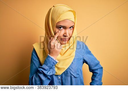 Young beautiful woman with curly hair wearing arab traditional hijab over yellow background Pointing to the eye watching you gesture, suspicious expression