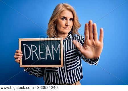Middle age beautiful blonde dreamer woman holding blackboard with dream message with open hand doing stop sign with serious and confident expression, defense gesture