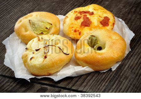 Small Pizzas Topped With Onion, Olives, Artichoke, And Tomatoes