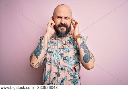 Handsome bald man with beard and tattoo wearing casual floral shirt over pink background covering ears with fingers with annoyed expression for the noise of loud music. Deaf concept.
