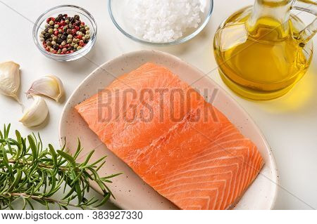Raw Chilled Salmon Fillet On A Plate, Fresh Rosemary, Garlic, Pepper, Sea Salt And Olive Oil On A Ki