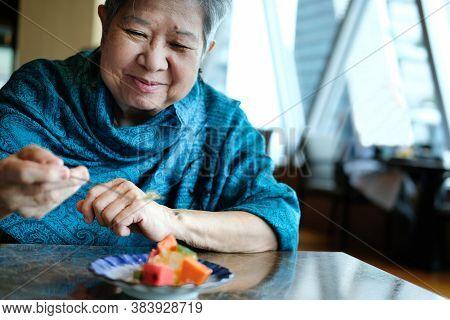 Old Asian Elderly Senior Elder Woman Eating Fruit At Restaurant. Mature Retirement Lifestyle