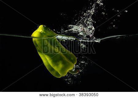 Green bellpepper falling into the water with a splash on a black background