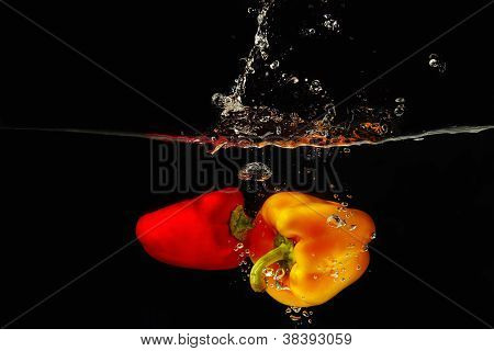 Fresh red and yellow bellpepper falling into the water with a splash on a black background