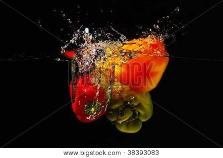 Fresh red green and yellow bellpepper falling into the water with a splash on a black background