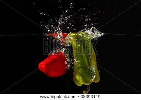 Red and green bellpepper falling into the water with a splash on a black background