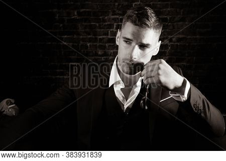 Portrait Of Handsome Man Wearing Tuxedo With Open Shirt Looking Away From Camera