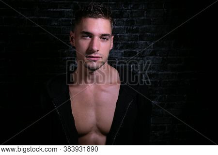 Portrait Of Handsome Serious Young Man Looking At Camera With Open Black Shirt Revealing Muscular Pe