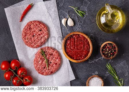 Fresh Raw Meat Burger Cutlet With Herbs And Spices On The Black Stone Board, Top View