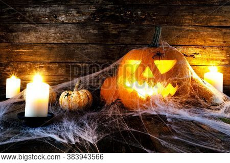 Jack O Lantern Halloween pumpkins, spiders on web and burning candles