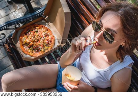 Beautiful, Young Woman Eating Pizza In The Street. The Concept Of Fast Food, Food Delivery And Lunch