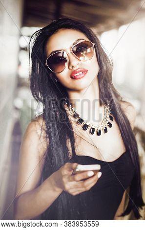 Beautiful stylish young woman walking through outdoor shopping mall wearing sunglasses holding phone.