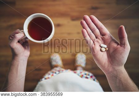 Sick Young Man In Nightwear Is Taking Pills And Drinking Hot Tea. Themes Health, Recovery, And Disea