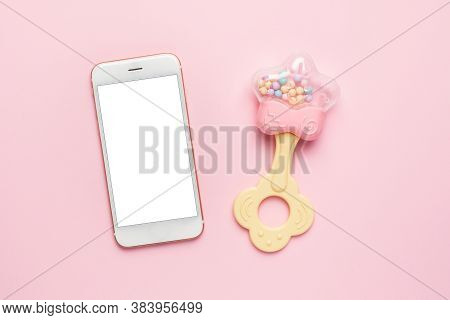 Mobile Phone And Baby Rattle With Teether On Pink Background