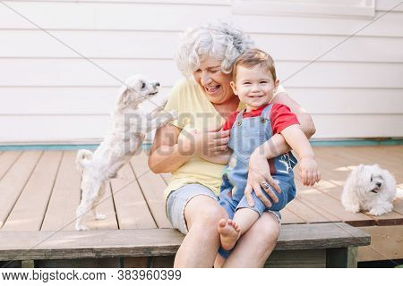 Grandmother Sitting With Grandson Boy On Porch At Home Backyard. Bonding Of Relatives And Generation