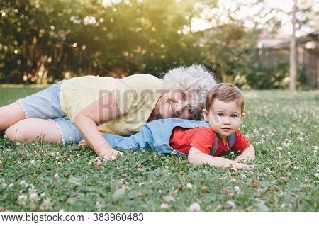 Grandmother Lying On Grass With Grandson Boy At Home Backyard. Bonding Of Relatives And Generation C