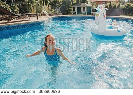 Cute Adorable Girl Swimming In Pool On Home Backyard. Kid Child Enjoying Having Fun In Swimming Pool