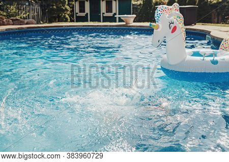 Water Drops Splash In Blue Water In Swimming Pool. Inflatable Swimming Large Toy Unicorn Floating In