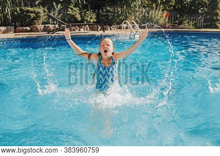 Cute Adorable Girl Swimming Splashing In Pool On Home Backyard. Kid Child Enjoying Having Fun In Swi