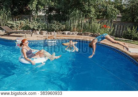 Mother With Daughters Children Relaxing In Swimming Pool On Home Backyard. Sisters Siblings Diving A