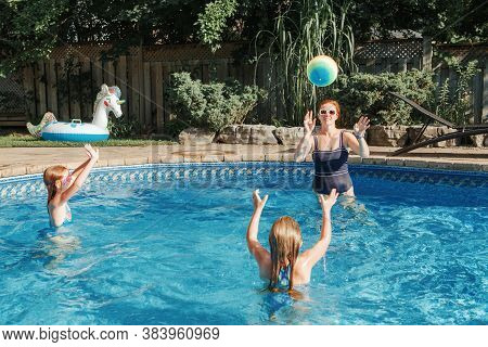 Mother Playing Ball With Daughters Children In Swimming Pool On Home Backyard. Mom And Sisters Sibli