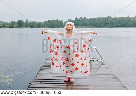 Girl Child In Rain Poncho With Red Maple Leaves Standing On Wooden Lake Dock. Kid Raising Arms Up Un