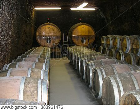 Wine Cellar With Barrels Of Wine From A French Winemaker. Aging Of Wine In Oak Barrels.