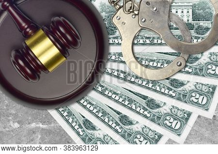 20 Us Dollars Bills And Judge Hammer With Police Handcuffs On Court Desk. Concept Of Judicial Trial