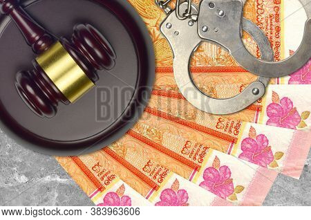 100 Sri Lankan Rupees Bills And Judge Hammer With Police Handcuffs On Court Desk. Concept Of Judicia