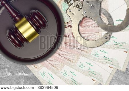 5000 Indonesian Rupiah Bills And Judge Hammer With Police Handcuffs On Court Desk. Concept Of Judici