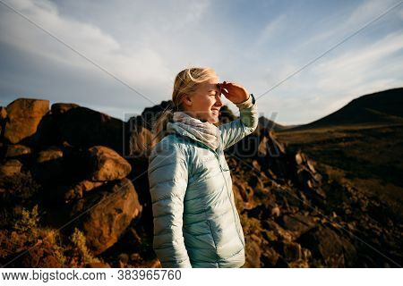 Young Caucasian Female Hiker Gazing While Standing On Top Of Mountain At Sunset.