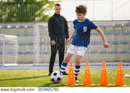 Kid Soccer Player Dribbling Through Cones. Boy In Soccer Uniform Practice With Ball. Child Kicking B