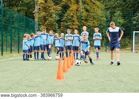 Kids Player Run And Kick Soccer Balls Between Soccer Chips In Soccer Training
