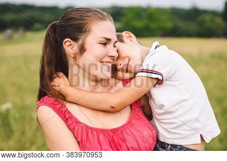 Mother And Son Hugging In Field. Happy Mother Embracing Her Son In Park. Mother Hugging Her Child. M