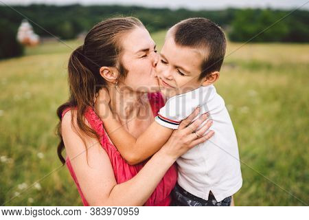 Young Caucasian Mother Holds In Her Arms Hugs And Hugs Her Son In Nature In Summer. Motherhood And F