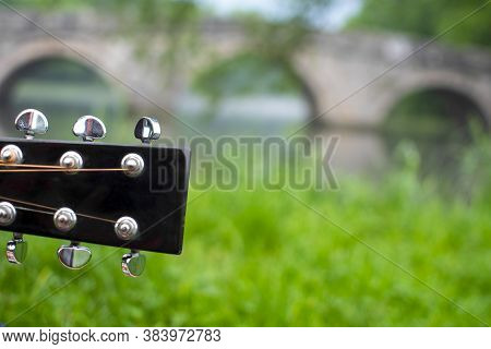 Closeup Of Guitar Headstock With Blured Roman Bridge In Background. Famous Touristic Place In Saraje